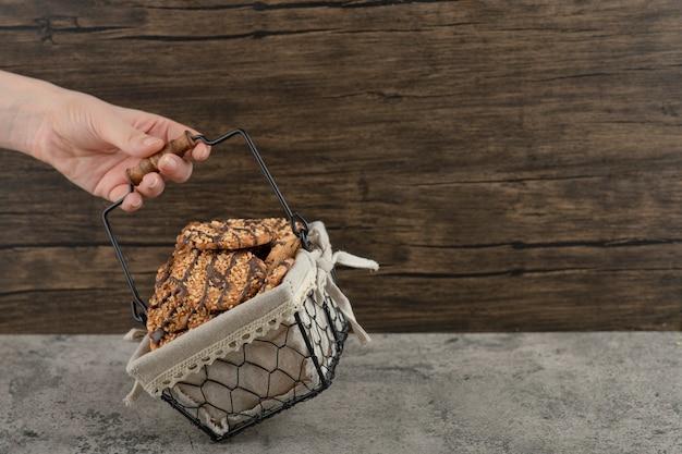 Weibliche hand, die korb von frisch gebackenen keksen auf marmoroberfläche hält.