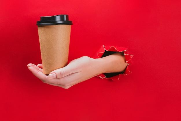 Weibliche hand, die kraftpapierkaffeetasse durch ein loch im rot hält.