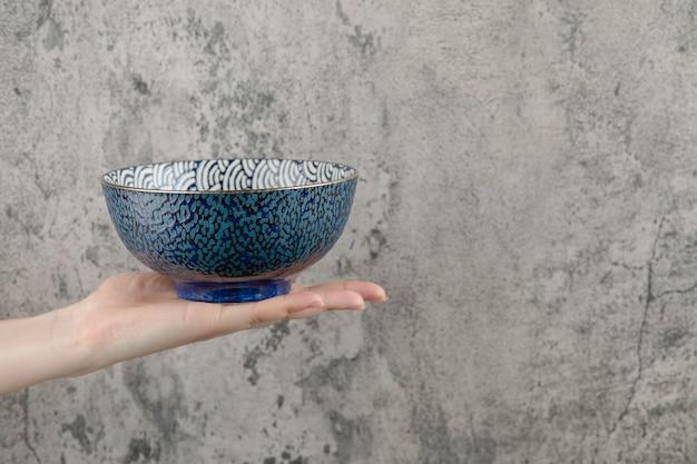 Weibliche hand, die leere blaue schüssel auf marmorhintergrund hält.