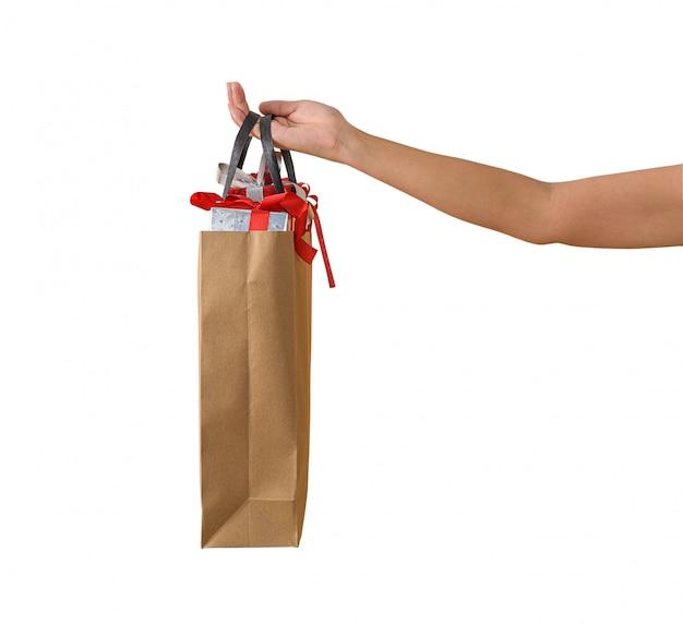 Weibliche hand, die leere braune papaer-einkaufstaschen voll von geschenkboxen verziert hält