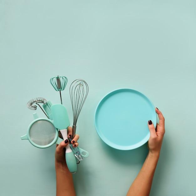 Weibliche hand, die leere schüssel auf blauem hintergrund mit kopienraum hält.