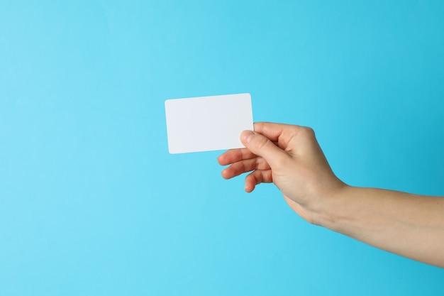 Weibliche hand, die leere visitenkarte auf blauem hintergrund hält