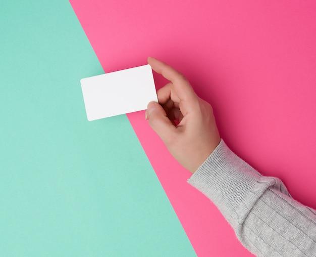 Weibliche hand, die leere weißbuchvisitenkarte hält