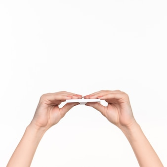 Weibliche hand, die leeres papier für aufzeichnungen auf weiß hält