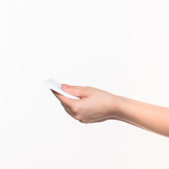 Weibliche hand, die leeres papier für aufzeichnungen auf weiß hält.