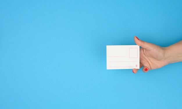 Weibliche hand, die leeres papierabzeicheneinsatz auf blauem hintergrund hält, kopienraum