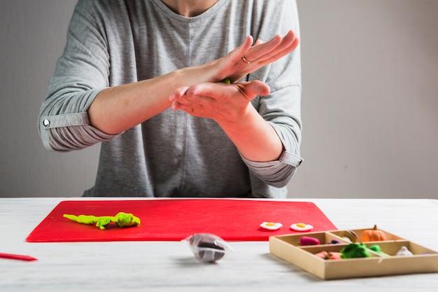 Weibliche hand, die lehm für die herstellung des handwerks knetet