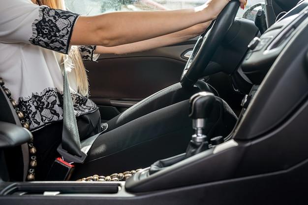 Weibliche hand, die lenkrad hält. nahaufnahme. reisekonzept