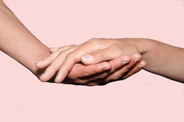 Weibliche hand, die männliche hand auf hintergrund hält.
