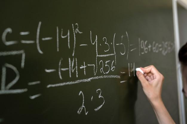 Weibliche hand, die mathematische formeln auf der klassentafel schreibt, nahaufnahme