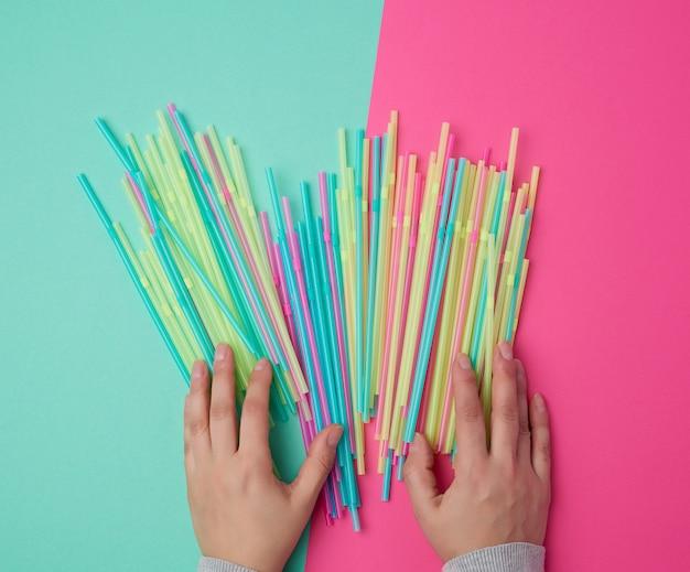 Weibliche hand, die mehrfarbige plastikcocktailrohre hält