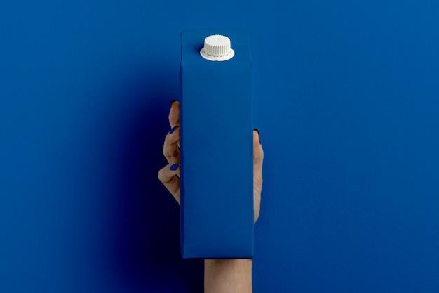 Weibliche hand, die milchbehälter auf klassischem blau hält