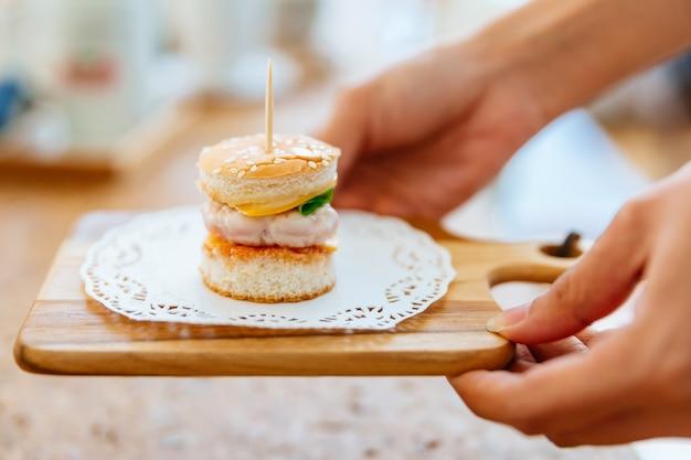 Weibliche hand, die mini chicken burger auf hölzernem hackendem brett mit unschärfehintergrund dient.