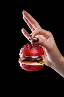 Weibliche hand, die miniburger als weihnachtsbaumspielzeug auf schwarzem hintergrund hält.