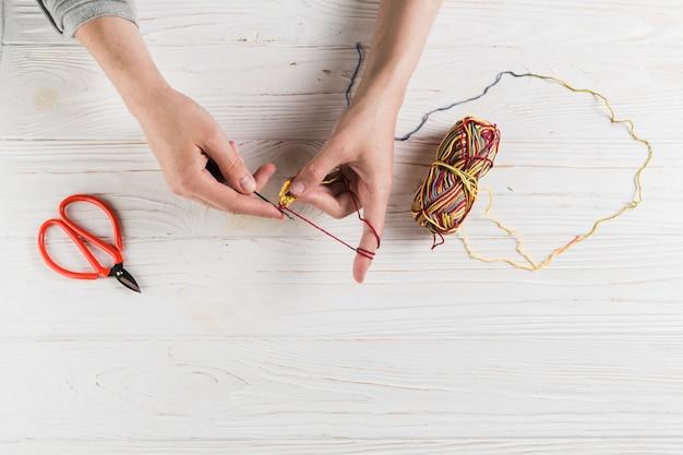 Weibliche hand, die mit bunter wolle auf holztisch strickt