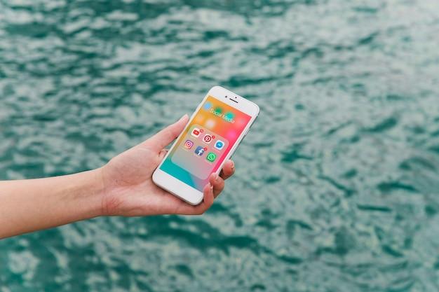 Weibliche hand, die mobiltelefon mit social media-benachrichtigungen auf schirm zeigt