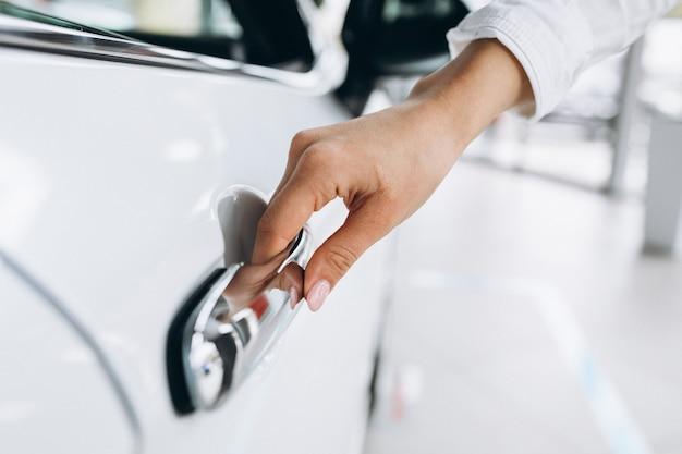Weibliche hand, die nahes hohes des autos öffnet