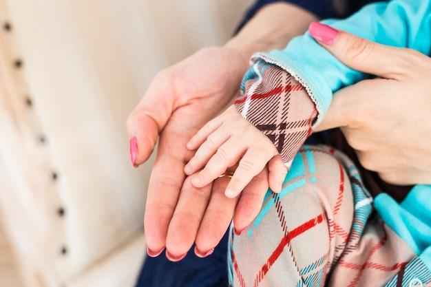 Weibliche hand, die neugeborene babyhand drinnen hält
