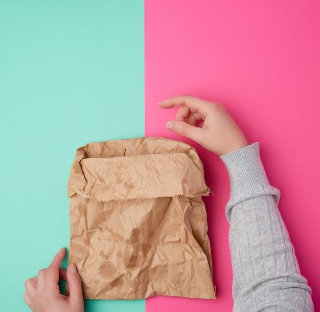 Weibliche hand, die offene braune papiertüte für die lebensmittelverpackung mit fettigen flecken hält