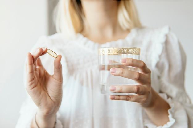 Weibliche hand, die omega 3-fischölergänzungskapsel und -glas wasser hält