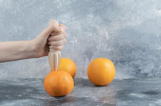 Weibliche hand, die orange auf marmortisch zusammendrückt.