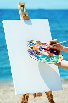 Weibliche hand, die palette mit farben und staffelei mit leinwand am strand hält