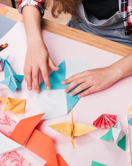 Weibliche hand, die papier bei der herstellung des dekorativen origamikunsthandwerks faltet