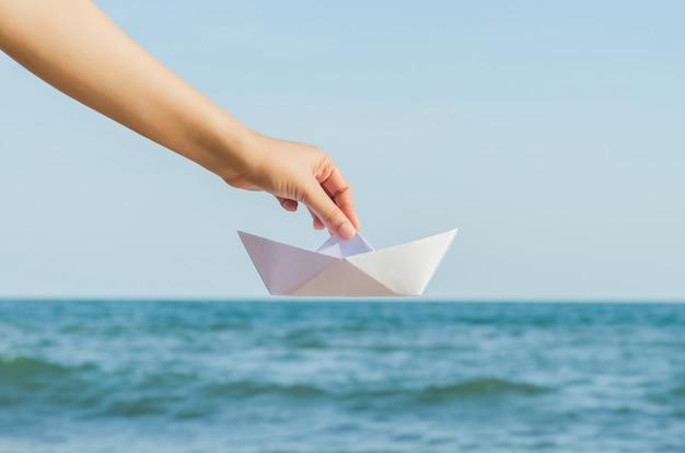 Weibliche hand, die papierboot auf dem seehintergrund hält