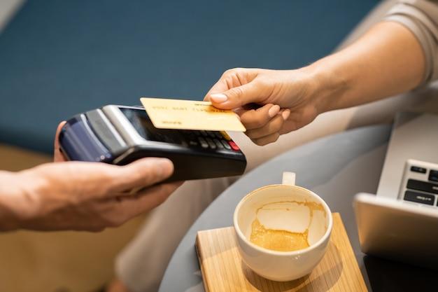 Weibliche hand, die plastikkarte über elektronischem zahlungsautomaten hält, der vom kellner gehalten wird, während für cappuccino im café bezahlt wird