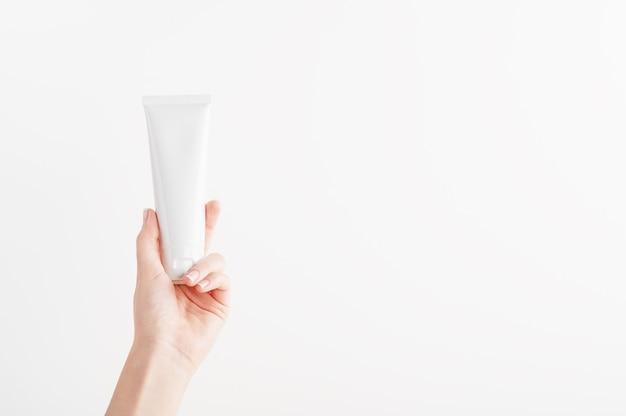 Weibliche hand, die plastikrohr ohne markenzeichen hält. flakon für creme, körperlotion, toilettenartikel.