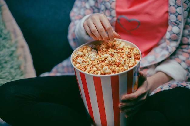 Weibliche hand, die popcorn von papier-eimernahaufnahme auswählt. nahaufnahme der frau, die popcorn am kino isst. weibliche hand, die popcorn im eimer am kino nimmt.