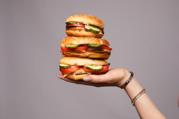 Weibliche hand, die pyramide von dem appetitanregenden burger drei lokalisiert an der grauen studiohintergrundnahaufnahme hält