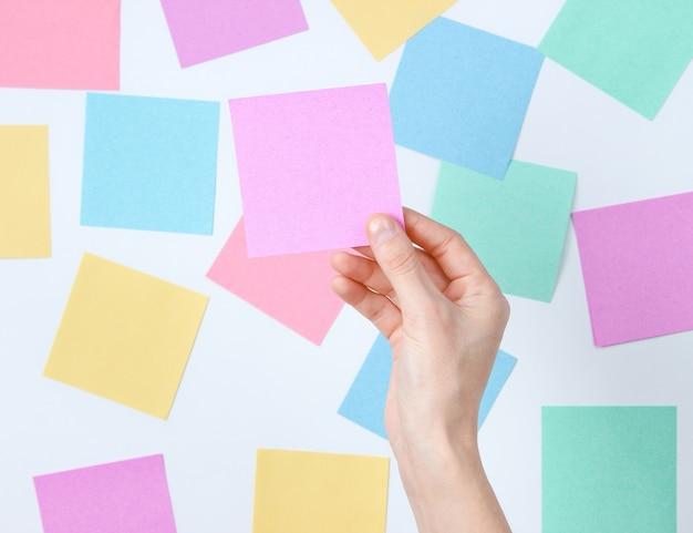 Weibliche hand, die rosa notizblatt des papiers auf einem weiß unter vielen farbigen blättern des papiers hält