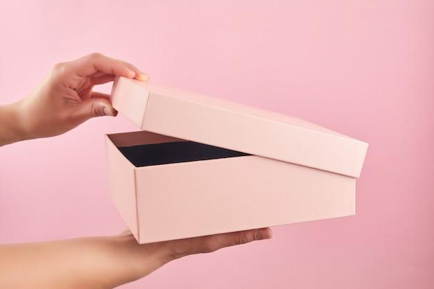 Weibliche hand, die rosa papierkastenpaket auf pastellhintergrund hält. überraschung in offener papierbox.