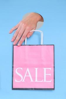Weibliche hand, die rosa papiertüte auf blau hält