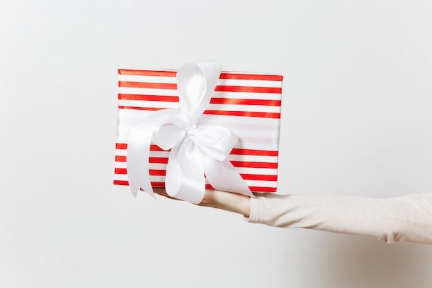 Weibliche hand, die rot gestreifte geschenkbox mit band und bogen hält. geschenk isoliert auf weißem hintergrundabschluß oben. valentinstag, geburtstag, internationaler frauentag, urlaubskonzept.