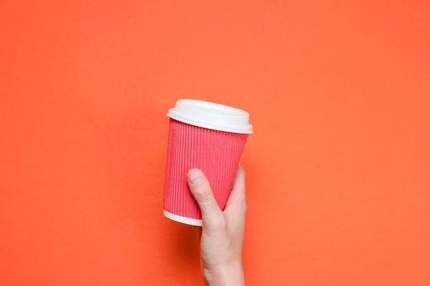 Weibliche hand, die rote papierkaffeetasse lokalisiert hält