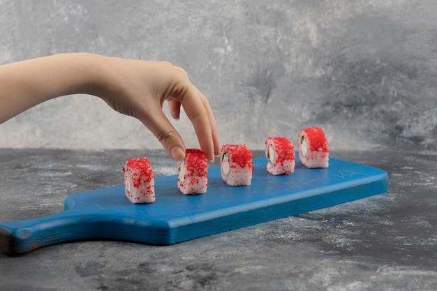 Weibliche hand, die rote sushi-rolle vom blauen schneidebrett pflücken