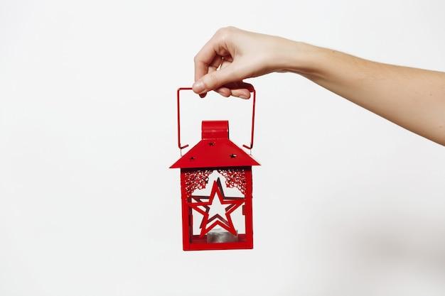 Weibliche hand, die rote weinlese-weihnachtslaterne mit kerzenständer lokalisiert auf weißem hintergrund hält. neujahrsfeiertag 2018 konzept.