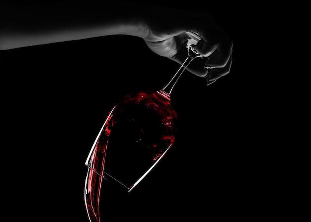 Weibliche hand, die rotwein von einem glas, konzeptstoppalkoholismus, über schwarzem hintergrund gießt