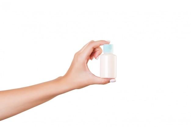 Weibliche hand, die sahneflasche hält