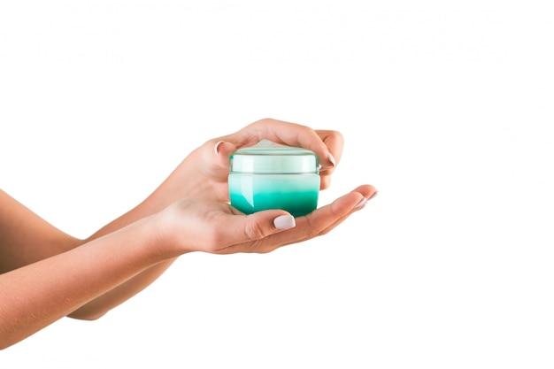 Weibliche hand, die sahneflasche lotion lokalisiert hält. kosmetische produkte des mädchenöffnungsglases auf weiß