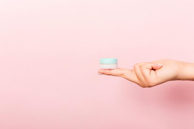 Weibliche hand, die sahneflasche lotion lokalisiert hält. mädchen geben kosmetische produkte des glases auf rosa hintergrund