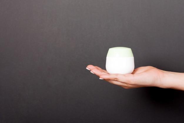 Weibliche hand, die sahneflasche lotion lokalisiert hält. mädchen geben kosmetische produkte des glases auf schwarzem hintergrund