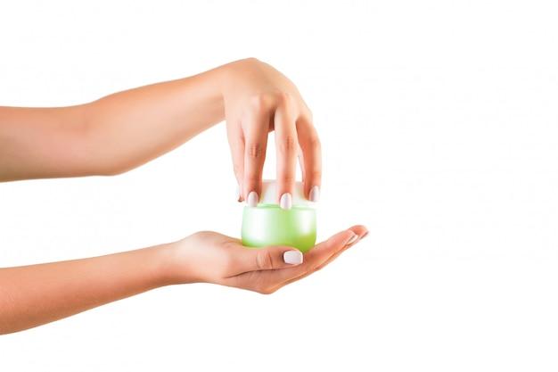 Weibliche hand, die sahneflasche lotion lokalisiert hält