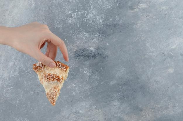 Weibliche hand, die scheibe des köstlichen kuchens auf marmorhintergrund hält.