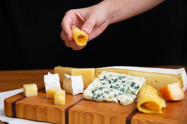 Weibliche hand, die scheibe käse vom holzbrett nimmt