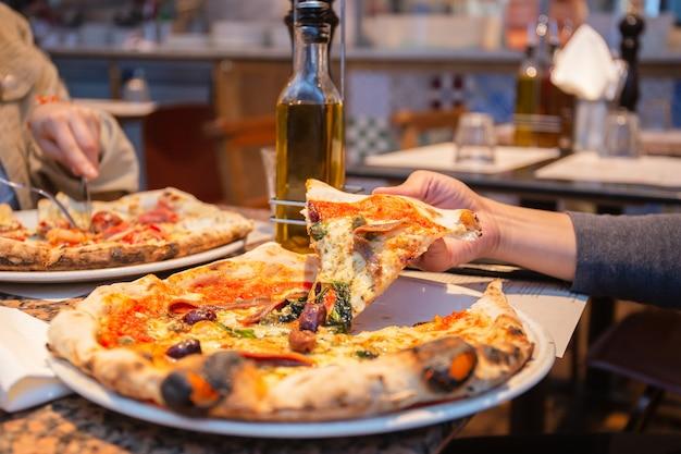 Weibliche hand, die scheiben der geschmackvollen pizza von der platte im restaurant nimmt.