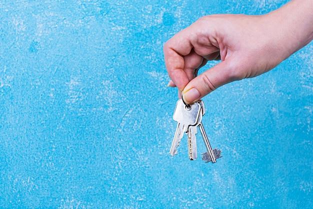 Weibliche hand, die schlüssel an der blauen wand hält