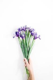 Weibliche hand, die schönen lila irisblumenblumenstrauß auf weißem hintergrund hält. flache lage, ansicht von oben.